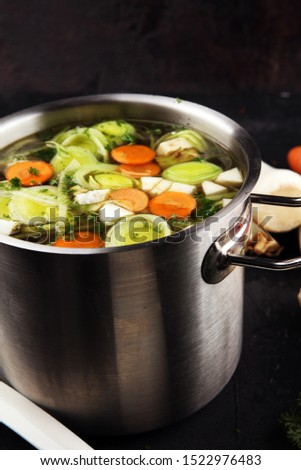 Broth with carrots, onions various fresh vegetables in a pot - colorful fresh clear spring soup. Rural kitchen scenery vegetarian bouillon or stock Сток-фото ©