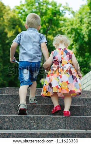 Brother aged four and sister aged two walking in park - stock photo