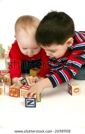 Brother and baby sister playing with blocks over white background.