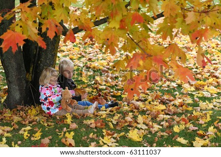 Brother and little sister sitting under the tree - stock photo