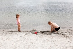 Brother and sister are playing on the lake, on a sandy beach near the water. A seven-year-old boy and a three-year-old girl in a swimsuit build sand castles. Children's friendship. Happy summer holida