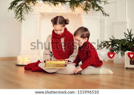 brother and sister at Christmas. Happy children at the fireplace