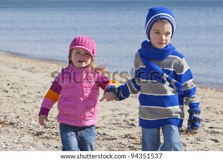 Brother and sister at the beach in winter