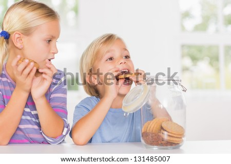 Brother and sister eating biscuits in the kitchen