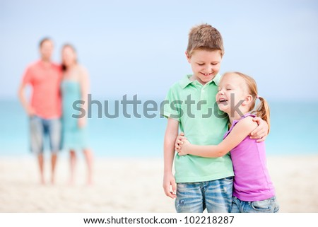 Brother and sister embracing each other while parents standing on background