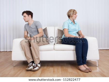 Brother and sister have had an argument and are sitting at opposite ends of a sofa