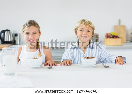 Brother and sister having breakfast in the kitchen stock photo