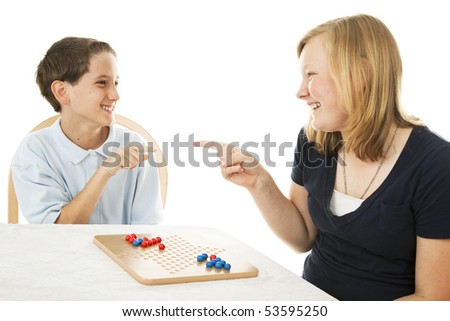 Brother and sister having fun playing board games.  Isolated on white.
