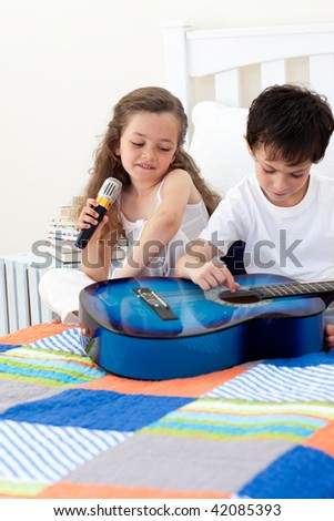 brother and sister having fun with a guitar in the bedroom stock photo