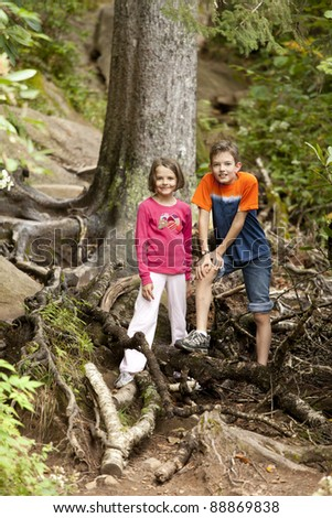brother and sister hiking in deep forest