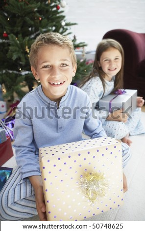 Brother and sister holding gifts sitting by christmas tree, portrait