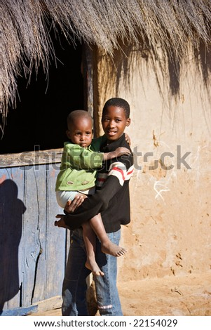 brother and sister in front of a hut  in an african village