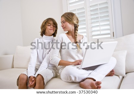 Brother and sister in white on sofa using laptop