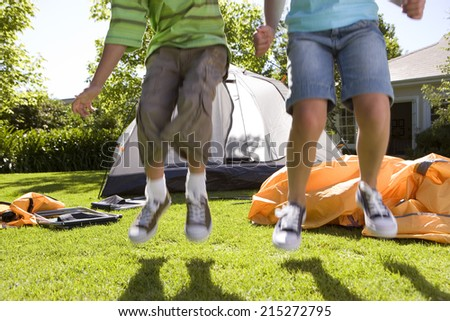 Brother and sister (8-10) jumping in front of incomplete dome tent on garden lawn, low section, front view