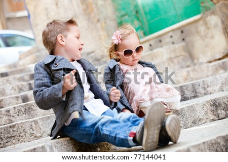 Brother and sister outdoors in city on beautiful spring day - stock photo