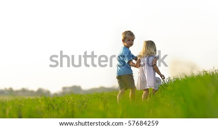Brother and sister play together in a green meadow