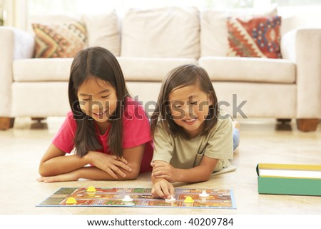 Brother and Sister Playing Board Game At Home