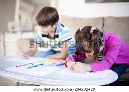 Brother and sister playing in the living room. Children drawing