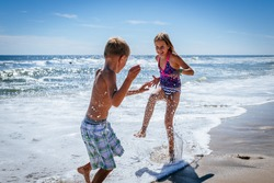 Brother and sister playing in the shore break on the beach during the hot summer vacation day.