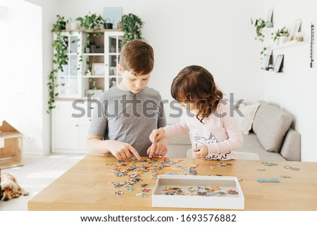 Brother and sister playing puzzles at home. Children connecting jigsaw puzzle pieces in a living room table. Kids assembling a jigsaw puzzle. Fun family leisure. Stay at home activity for kids.