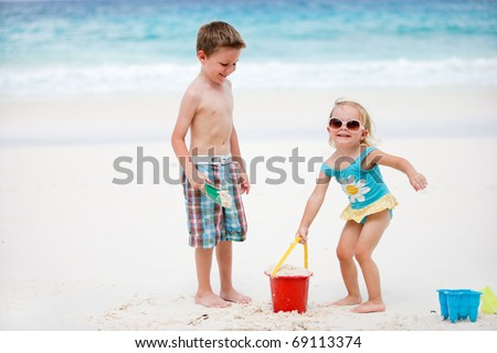 Brother and sister playing together on send beach - stock photo