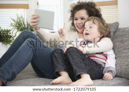 Brother and sister relaxing on sofa with digital tablet