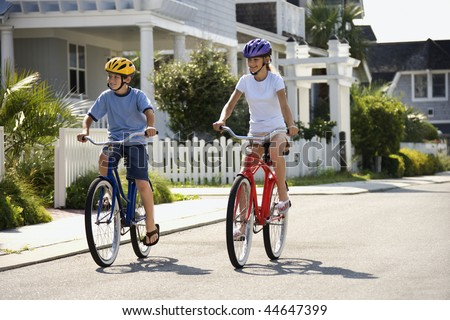 Brother and sister riding bikes together on street.  Horizontally framed shot.