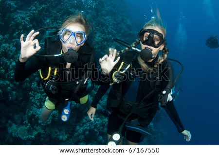 brother and sister scuba dive together