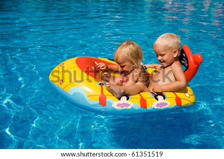 Brother and sister sitting in the inflatable boat in the swimming pool.