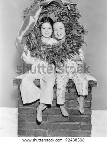 Brother and sister sitting on a chimney