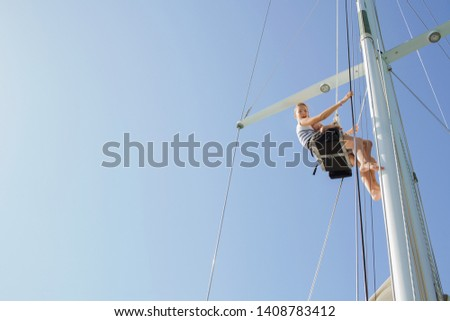 Brother and sister sitting together high up climbing mast, luxury sailing yacht, smiling happy against sunny blue sky, outdoors. Family summer adventure, boat activities leisure recreation lifestyle. #1408783412