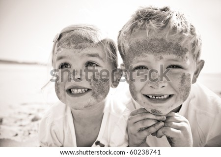 Brother and sister smile at the camera, brightly lit, on the beach, faces covered in sand.