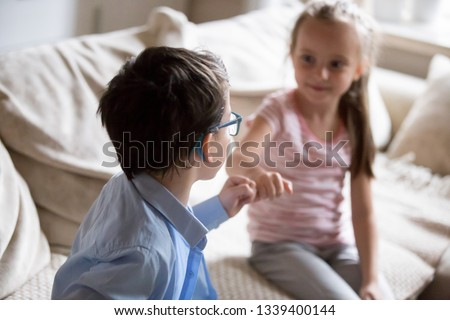 Brother and sister squeeze little fingers as sign of reconciliation. Boy and girl put up after having fight, conflict, quarrel at home Siblings relationship, kids interaction, family lifestyle concept