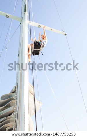 Brother and sister together high up climbing mast on luxury sailing yacht, joyful expressions against sunny blue sky, outdoors. Family summer adventure, boat activities leisure recreation lifestyle. #1469753258