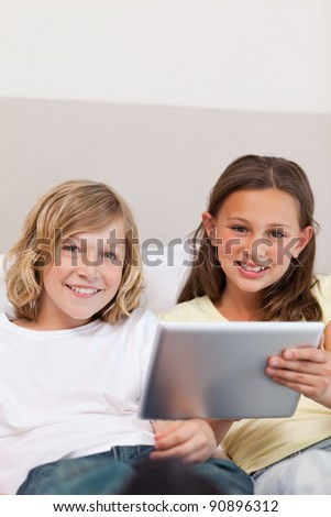 Brother and sister using tablet on the couch