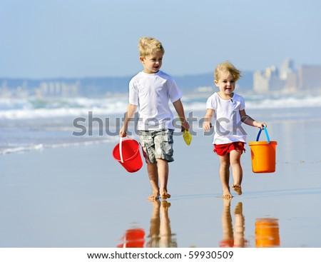 Brother and sister walk along the ocean edge looking for shells