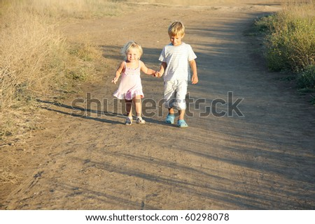 brother and sister walking by country road