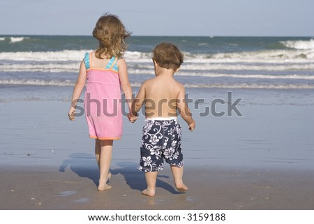Brother and sister walking on a beach