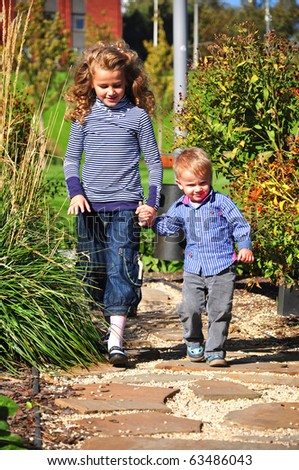 Brother and sister walking together  in the park