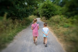Brother and sister walking together on a narrow paved path in the countryside in summer