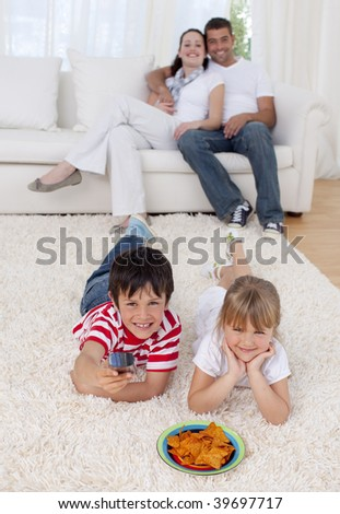 Brother and sister watching television on floor in living-room with their parents on sofa