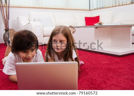 Brother and sister with laptop laying on the floor at home