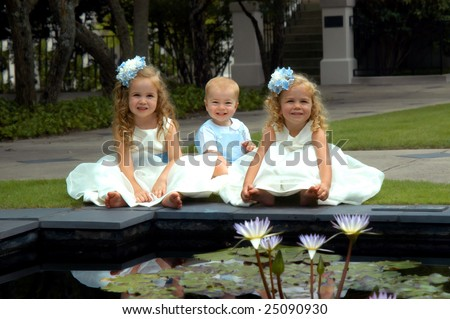Brother and two sisters pose in blue and white.  All three sit in front of a water lilly pool.
