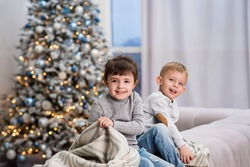 brother ans sister twins sitting on the sofa having fun in the living room and the new year pine-tree on the background