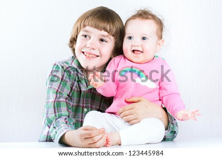 Brother hugging his baby sister, both wearing green and pink shirts