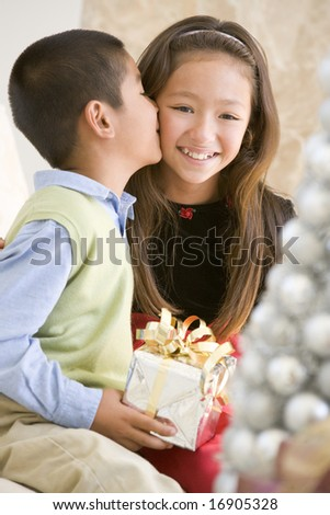 Brother Kissing His Sister On The Cheek,And Holding A Christmas Gift