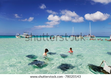 Brother & sister enjoy playing with the stingrays at the sandbar off Grand Cayman