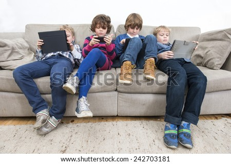 Brothers and sister using electronic devices while slouching on sofa at home