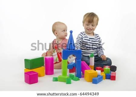 Brothers and sisters play with plastic cubes, on white background.