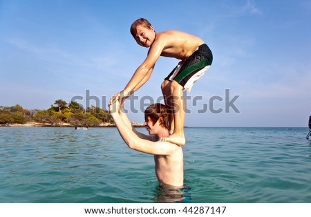 brothers are playing together jumping from shoulder in the sea  in crystal clear water with blue sky - stock photo